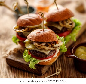 Hamburgers, homemade burgers with grilled buns with  addition of beef cutlet, fresh lettuce, tomato,pickled cucumber,  grilled onion, cheese and spicy sauce on a wooden rustic table