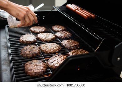 Hamburgers and hot dogs cook on flame charred backyard grill