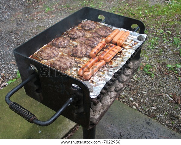 Hamburgers and hot dogs on a charcoal grill