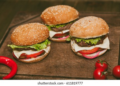 Hamburgers and tomatoes on a wooden board