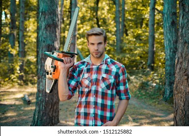 Hamdsome man Lumberjack with an axe or chainsaw in a plaid shirt. Lumberjack with chainsaw in his hands. Stylish young man posing like lumberjack. Deforestation