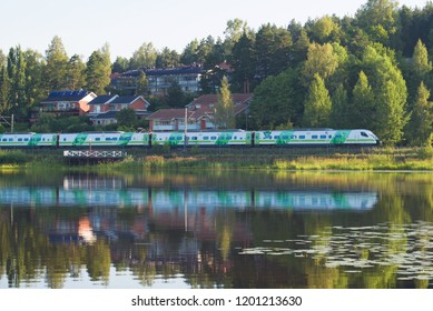 "HAMEENLINNA, FINLAND - JULY 24, 2018: The passenger high-speed train Sm3 ""Pendolino"" passes across the coast of the lake Vanayavesi"