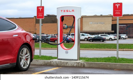 HAMILTON, CANADA - April 23rd, 2019: Red Tesla Model S plugged-in to Tesla Supercharger Stall, with Tesla Vehicle Charging sign beside at CF Limeridge in Hamilton, Ontario.
