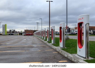 HAMILTON, CANADA - April 23rd, 2019: Tesla Supercharger Station with 20 Stalls and Tesla Model S charging in the background at CF Limeridge, Hamilton, Ontario.