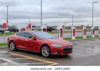 HAMILTON, CANADA - April 23rd, 2019: Red Tesla Model S at Tesla Supercharger Station in Hamilton, Ontario.