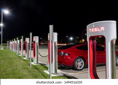 HAMILTON, CANADA - August 31, 2019: Tesla Supercharger Station at night with Tesla Model S's plugged-in and charging in the background.