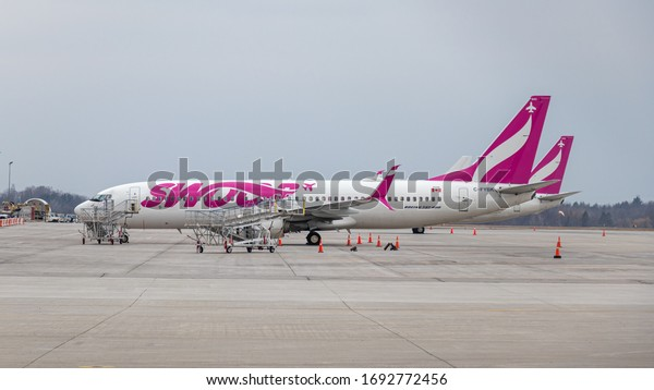 HAMILTON, CANADA - March 26, 2020: Swoop Boeing 737-8, a low-cost carrier owned by WestJet seen parked at Hamilton Intl. Airport on a cloudy day.