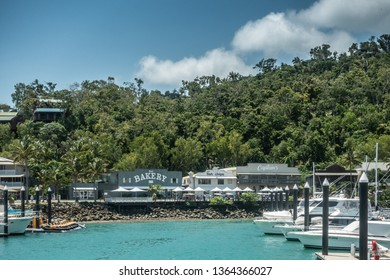 Hamilton Island, Australia - February 16, 2019: Bakery, captains and other eateries on Front Street behind row of white boats moored in marina. Back is greeen foliage of forest under blue sky. Azure