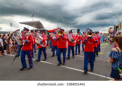 Hamilton / New Zealand - December 8 2019: A Brass Band in Red Uniforms Marching Down the Street. Photographed at a Christmas Parade