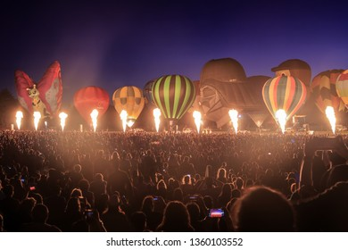 "Hamilton / New Zealand - March 23 2019: A Row of Hot Air Balloons at Night, Lit Up By Bursts of Flame From Their Burners. Balloons Over Waikato Festival ""Nightglow"""