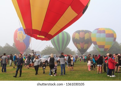 Hamilton / New Zealand - March 23 2019: Bright and Colorful Hot Air Balloons, Tethered to the Ground on a Misty Day, Surrounded by a Crowd. Balloons Over Waikato Festival