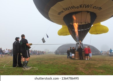 Hamilton / New Zealand - March 23 2019: A Hot Air Balloon Firing its Burner, With Ground Crew Holding its Mooring Ropes. Balloons Over Waikato Festival