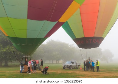 Hamilton / New Zealand - March 23 2019: Two Colorful Hot Air Balloons on the Ground on a Misty Day, With People Milling Around the Baskets. Balloons Over Waikato Festival