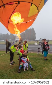 "Hamilton / New Zealand - March 23 2019: Hot Air Ballooning. A Female Pilot Demonstrates a ""Chariot"" (With a Single Seat) Balloon to a Little Child. Balloons Over Waikato Festival"
