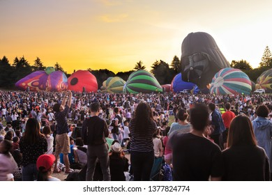 Hamilton / New Zealand - March 23 2019: A Row of Hot Air Balloons, One Shaped Like Darth Vader's Helmet, Against a Sunset Sky. A Huge Crowd Watches Them Inflate. Balloons Over Waikato Festival