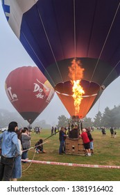 "Hamilton / New Zealand - March 23 2019: Hot Air Balloons at ""Balloon Over Waikato"" Festival. The Foreground Balloon is Releasing Flame From its Burner, Inflating the Balloon"