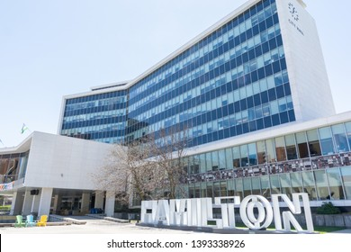 Hamilton, Ontario / Canada - May 08, 2019: The front of City Hall (Hamilton) Municipal Service Centre. The Hamilton signature sign is also captured in the shot.