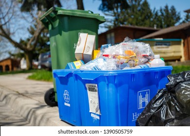 Hamilton, Ontario / Canada - May 2019: Overfilled garbage bins seen at curb side for garbage pick up day in the city.