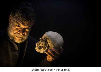 In a Hamlet pose, a bearded crazy old man looks into a skull's eyes in Halloween.