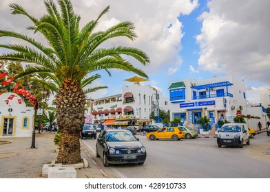 HAMMAMET, TUNISIA - Oct 2014: Street with date palms, trees and white buildings on October 6, 2014 in Hammamet, Tunisia.
