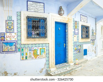 HAMMAMET, TUNISIA - SEPTEMBER 6, 2015: The facade wall of the art gallery decorated with pictures and arabic texts made on glazed tiles, on September 6 in Hammamet.