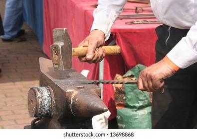 Hammer and anvil, blacksmith hammering iron