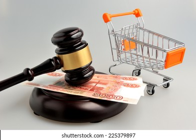 Hammer of auctioneer with pushcart and money on gray background