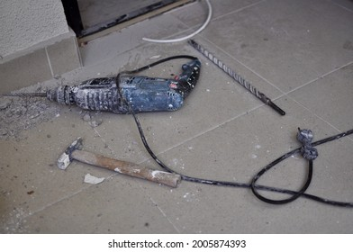 Hammer, chisel and electric drill lying on the tile floor. Renovation. Home improvement. Do It Yourself apartment repairing.