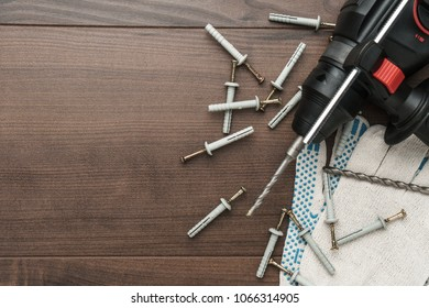 hammer drill and dowels on the wooden background with copy space