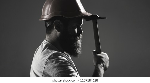 Hammer hammering. Builder in helmet, hammer, handyman, builders in hardhat. Handyman services. industry, builder man. Bearded man worker with beard, building helmet, hard hat. Black and white.