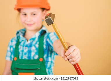 hammer in hand of small girl repairing in workshop. Foreman inspector. Little girl in helmet with hammer. Kid worker in hard hat. Labor day. 1 may. repair shop. fixing everything.
