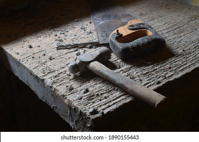 Hammer, Handsaw, Drillbit. Tools On top of a concrete table