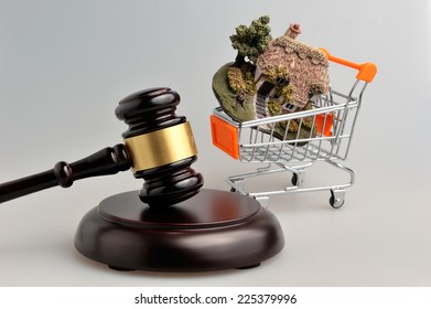Hammer of judge with model of house in trolley on gray background