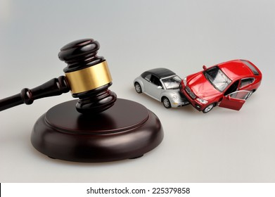 Hammer of judge with models of car accident on gray background