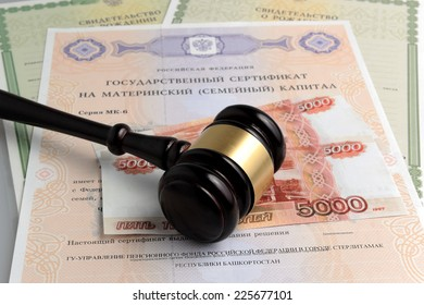 Hammer of judge with money, maternal and birth certificates on gray