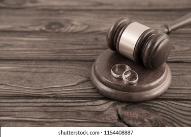 hammer of the judge, a pair of gold wedding rings on the background of a wooden table. family law, divorce.