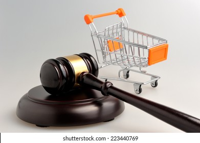 Hammer of judge and pushcart on gray background