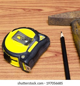 hammer measuring tape and pencil concept tools on wood background