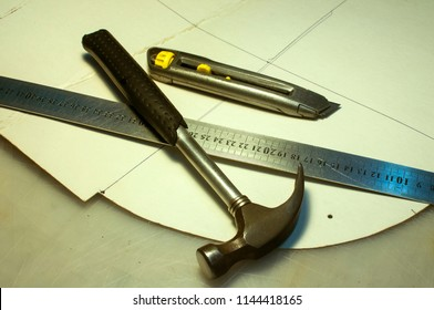 Hammer, metal ruler, cutter knife and cardboard cuts as tools in workshop production of leather goods