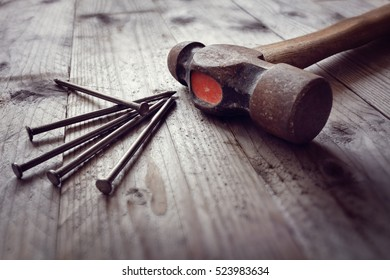 Hammer and nails on floorboards concept for construction, diy, tools and home improvement