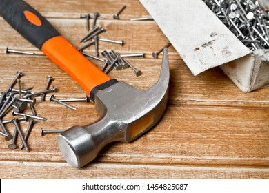 Hammer and nails scattered on wooden background. Joinery concept
