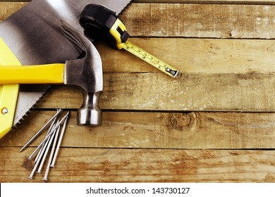 Hammer, nails, tape measure and saw on wood