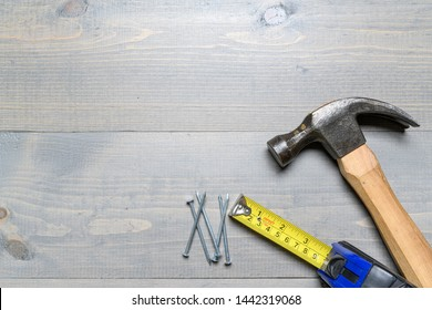 Hammer, nails and a yellow tape measure on wood