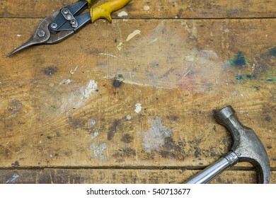 Hammer and pointy nose pliers on worn wooden workshop background