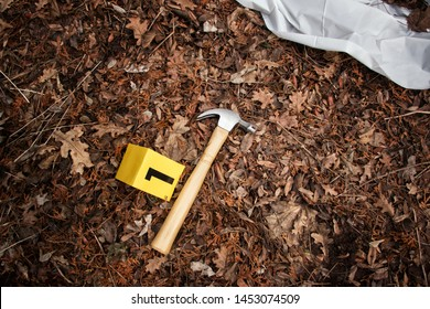 Hammer, a potential murder weapon at a violent crime scene, next to a body under a sheet. With evidence markers.