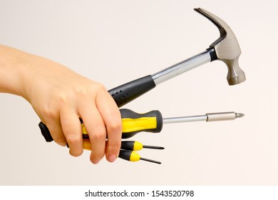 Hammer and screwdriver in hand on a white background. Outstretched construction tools