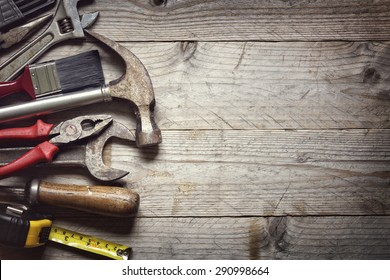 Hammer, screwdriver, wrench, tape measure, paint brush construction tools on wooden background with space for copy
