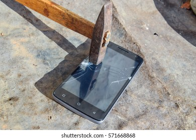 Hammer and smartphone. The screen of the smartphone, a broken hammer. The destruction of the phone.