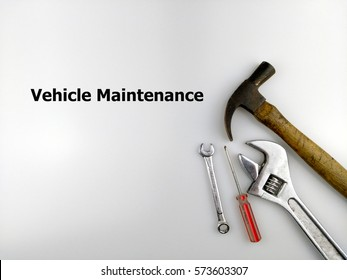 Hammer, spanner and screwdriver with text vehicle maintenance isolated on white background.