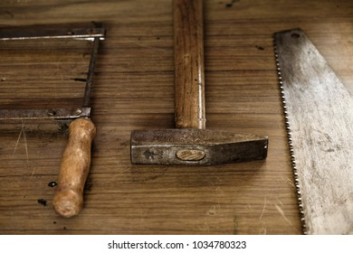 Hammer and two saw blades on a wooden bench, aligned